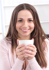 Pretty happy relaxed young lady sitting with coffee cup on couch