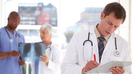 Serious doctor writing on his clipboard in front of colleagues