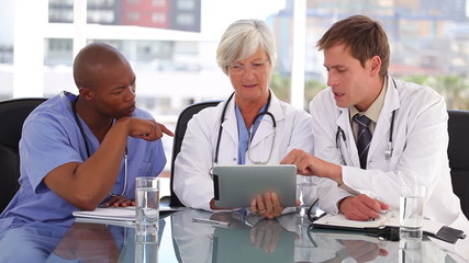 Mature doctor using a touchscreen with her colleagues