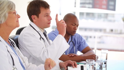 Serious doctor raising his finger to ask a question