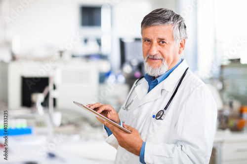 Senior doctor using his tablet computer at work (color toned ima