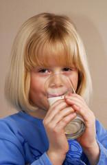 Pequeña niña bebiendo un vaso de leche.