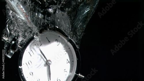 Alarm clock in a super slow motion falling in water
