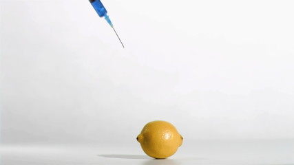 Syringe in super flow motion falling in a lemon