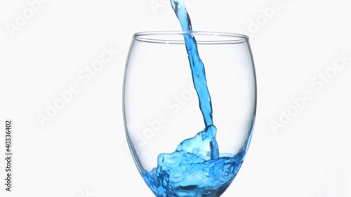 Blue liquid in super slow motion flowing in a wine glass