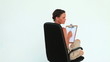 Woman holding a clipboard turning on her chair