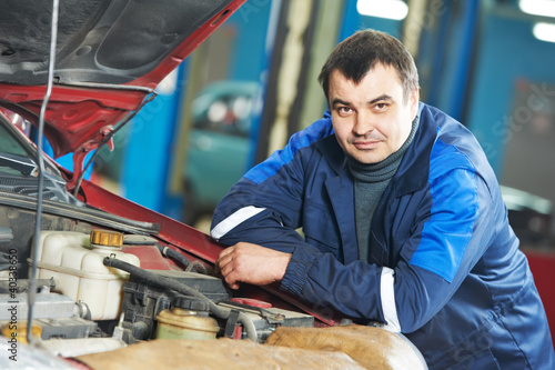 happy mechanic technician at service station
