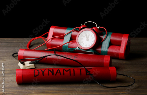 Timebomb made of dynamite on wooden table on black background