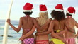 Four women standing while wearing Christmas hats