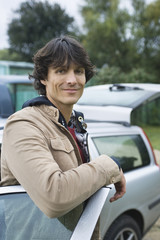 Young man standing by car, smiling, portrait