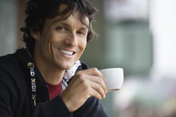 Young man drinking tea, portrait