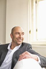 Businessman sitting on sofa, smiling