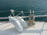 A sailing boat with white fenders