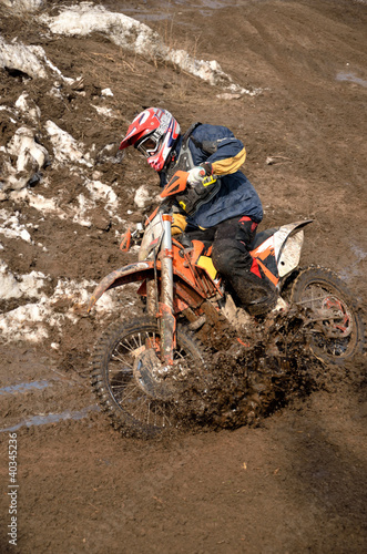 Motocross racer is turning in gauge line with a spray of dirt