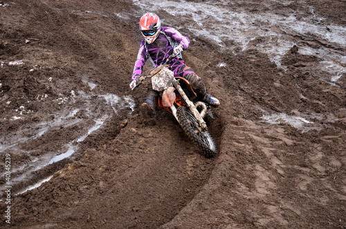 Rider at the beginning of rut turning sandy motocross track