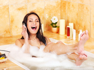 Woman listening to music in bubble  bath.