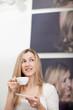 Frau trinkt Kaffe zuhause