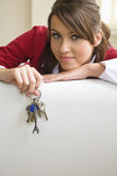 Young woman holding key ring with keys, portrait