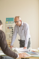 Businessmen looking at blue print in office