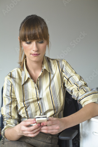 Mid adult woman holding mobile phone, messaging