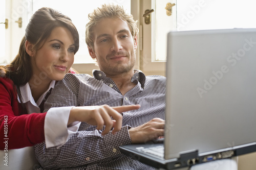 Friends using laptop, smiling