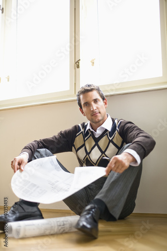 Businessman sitting on hardwood floor, holding blue print