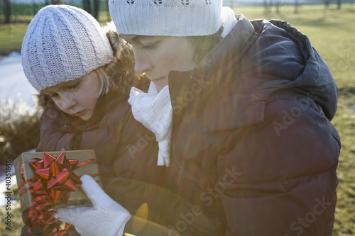 Mother with daughter looking at gift