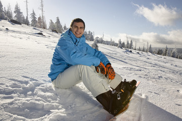 Young man sitting on snow, smiling, portrait