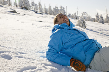 Young man lying on snow, smiling, side view