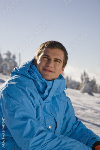 Young man sitting on snow, smiling