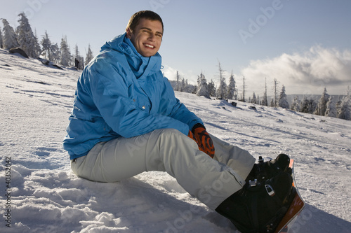 Young man sitting on snow, smiling, side view