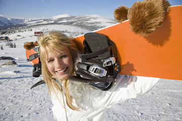 Young woman holding snowboard on shoulders, smiling, portrait