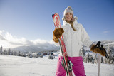 Young woman holding ski and ski pole, portrait