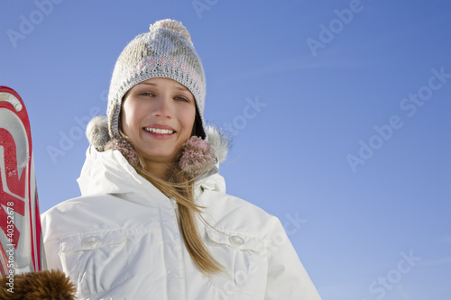 Young woman holding ski, portrait
