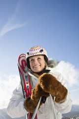 Young woman holding ski pole, smiling