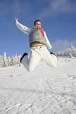 Young man jumping above snow