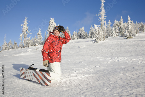 Young man kneeling on snow
