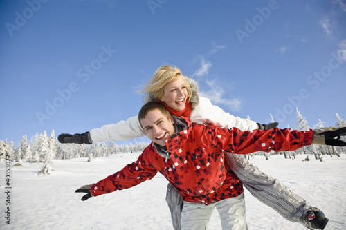 Young man giving piggyback to young woman
