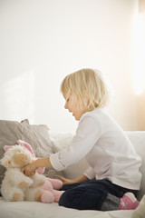 Girl playing with stuffed toys on sofa