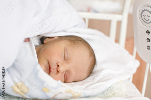 Baby sleeping on bed with red spots on face, close-up