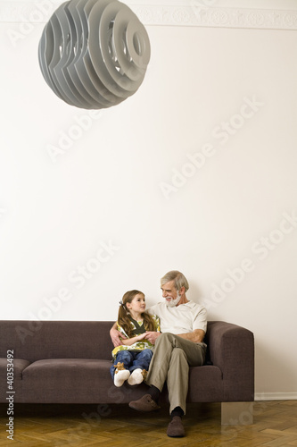 Senior man sitting with granddaughter on sofa