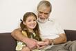 Senior man sitting with granddaughter on sofa, smiling