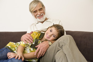 Girl lying on grandfather's leg, smiling
