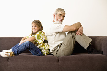 Senior man and girl sitting back to back on sofa