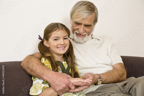 Senior man sitting with granddaughter on sofa, smiling