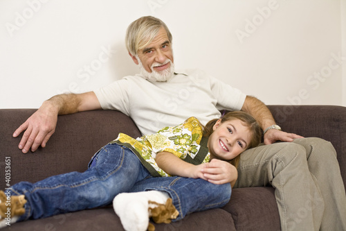 Girl resting on grandfather's leg, smiling, portrait