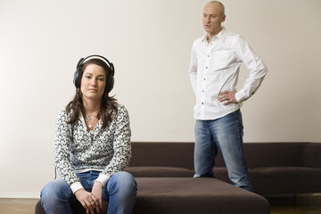 Woman wearing headphones listening to music while man standing