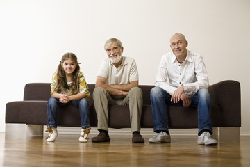 Family sitting together on sofa, smiling