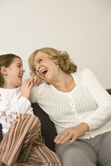 Senior woman sitting with granddaughter on sofa, smiling