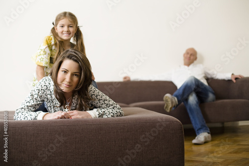 Girl sitting on woman's back while man relaxing in background